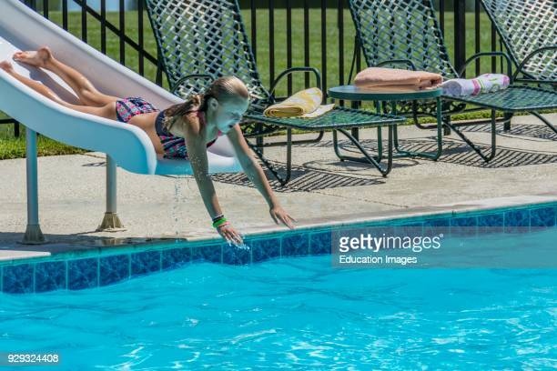 Young girl sliding down a pool slide