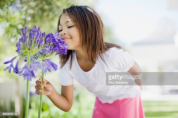 young girl smelling flower - smelling stock pictures, royalty-free photos & images