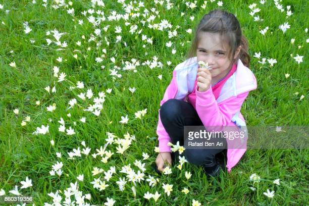 Young girl smelling fresh flowers