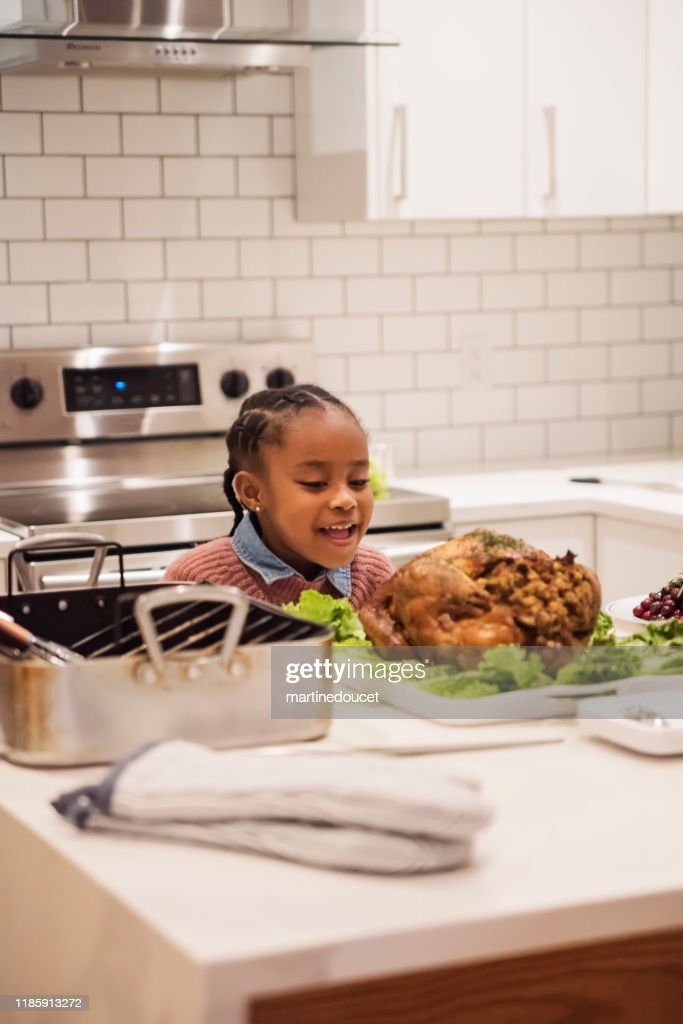 Young girl smelling the turkey preparing Thanksgiving dinner. : Stock Photo