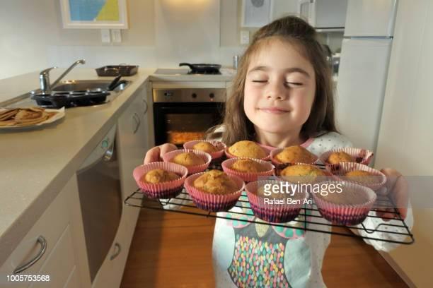 young girl smells fresh baked muffins - rafael ben ari 個照片及圖片檔