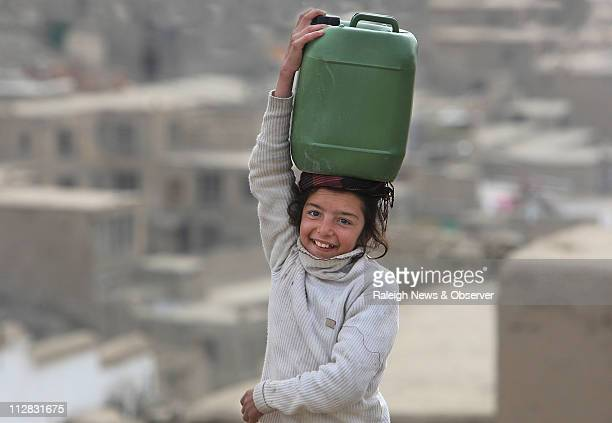 A young girl smiles as she makes her way to a meeting point where she will get water for her family's home located above Kabul Afghanistan November 8...