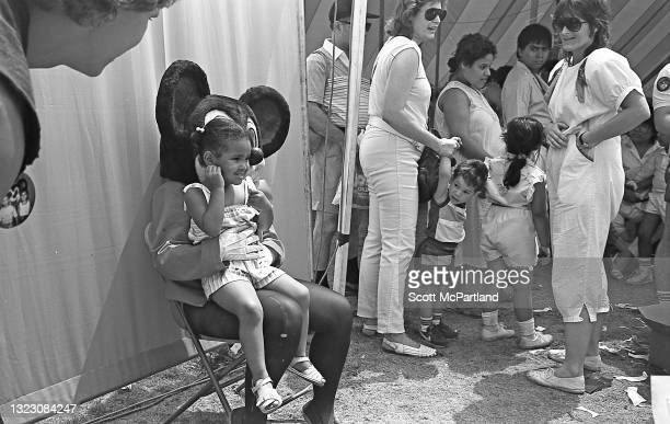 Young girl smiles as she sits on the lap of 'Mickey Mouse' in Flushing Meadows Park, in the Corona neighborhood, Queens, New York, New York, June 29,...