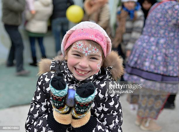 A young girl smiles holding an ornament during a New Years celebration at a humanitarian assistance center in Kiev on December 29 2014 Thousands of...