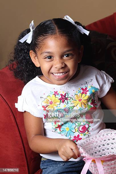 young girl smiling and holding hat - nanette j stevenson stock photos and pictures