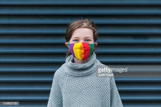 young girl smiling behind her rainbow mask - obscured face stock pictures, royalty-free photos & images