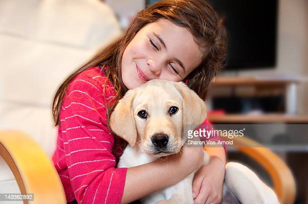 Young girl smiling cuddling labrador puppy