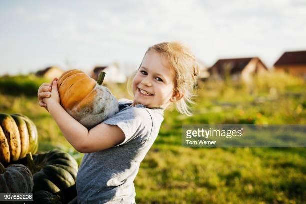 Young Girl Smiling Holding Freshly Harvested Pumpkin