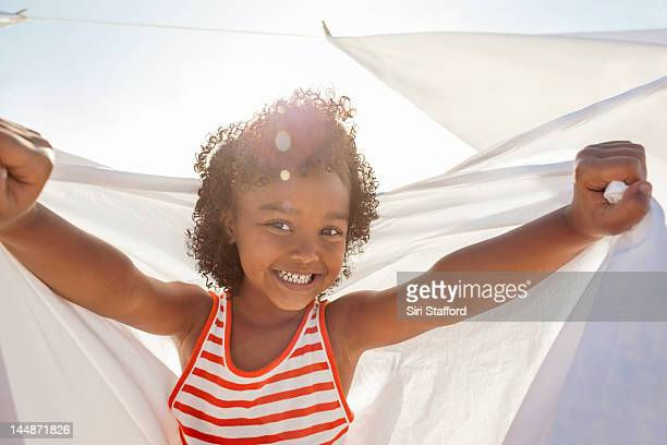 Young girl smiling, holding white sheet