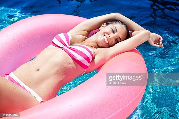 young girl smiling in inner tube in a luxury pool