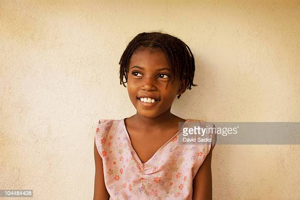 young girl smiling outside of school - haiti stock-fotos und bilder