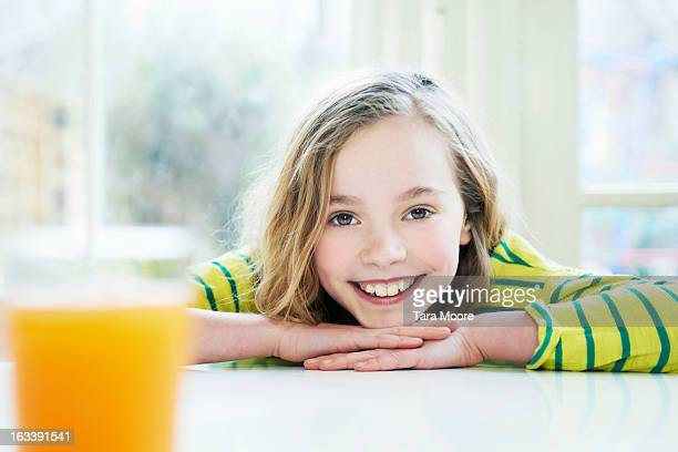 young girl smiling with glass of juice in kitchen