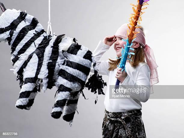 Junges Mädchen lächelnd mit Piñata in den Vordergrund