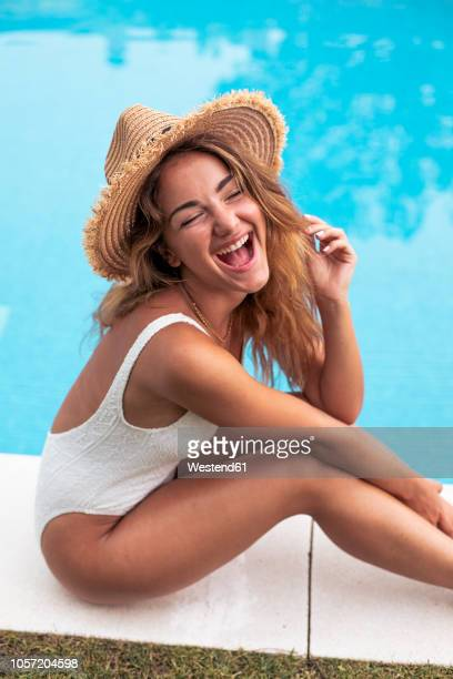 young girl smiling with straw hat and swimsuit sitting at poolside - swimwear stock pictures, royalty-free photos & images