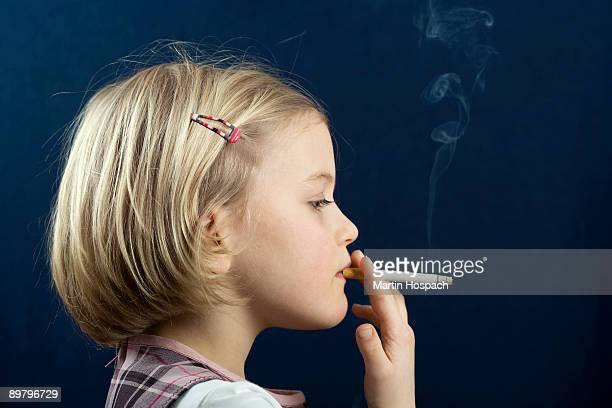 a young girl smoking a cigarette - little girl smoking cigarette stock photos and pictures