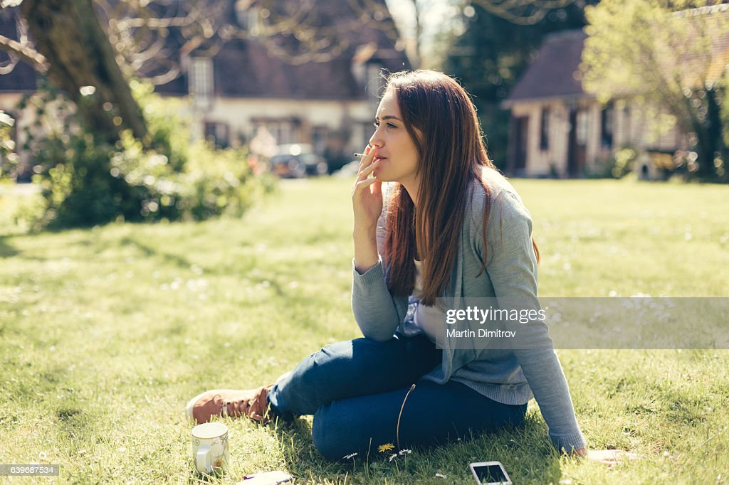 Young girl smoking cigarette : Stock Photo