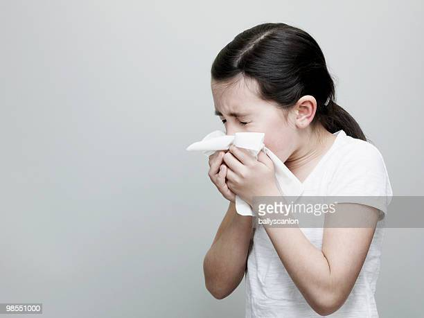 Young Girl Sneezing and Blowing Nose With Tissue.