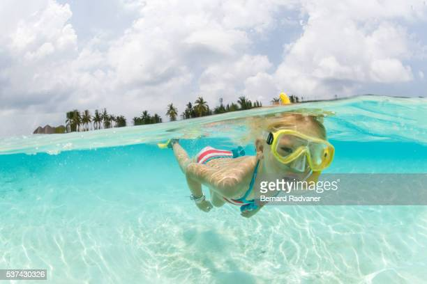 young girl snorkeling at the surface under a maldivian island