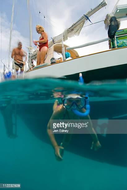 A young girl snorkels next to her boat in Georgetown, Exumas