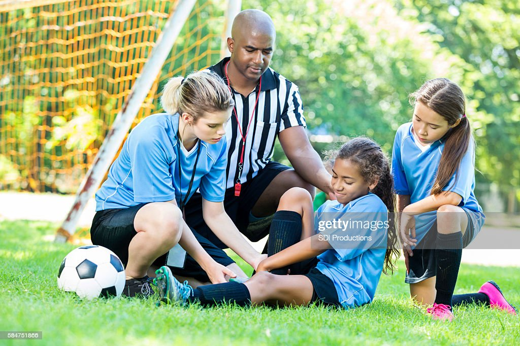 Young girl soccer player got hurt during the game : Stock Photo