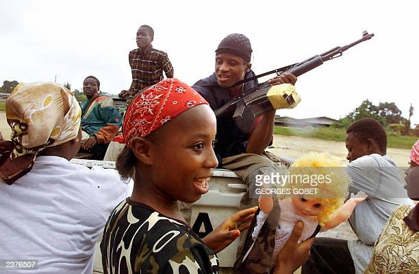 A young girl soldier fighting with the government forces plays with a doll 30 July 2003 alongside other fighters just northeast of Monrovia where...