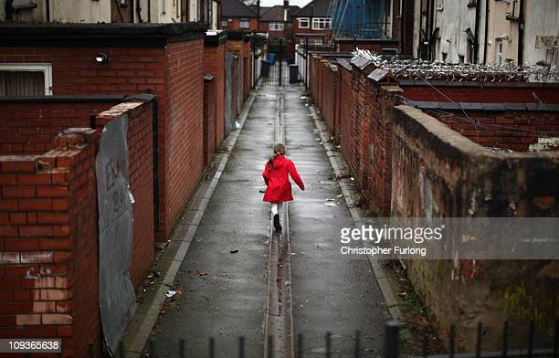 A young girl spends the half term school holiday playing in an an alleyway in the Gorton area of Manchester on February 23 2011 in Manchester England...