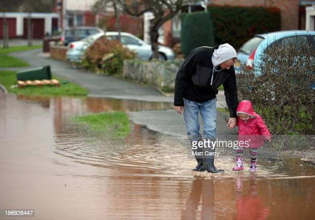A young girl splashes through flood water in the centre of the village of Ruishton near Taunton on November 25 2012 in Somerset England Another band...