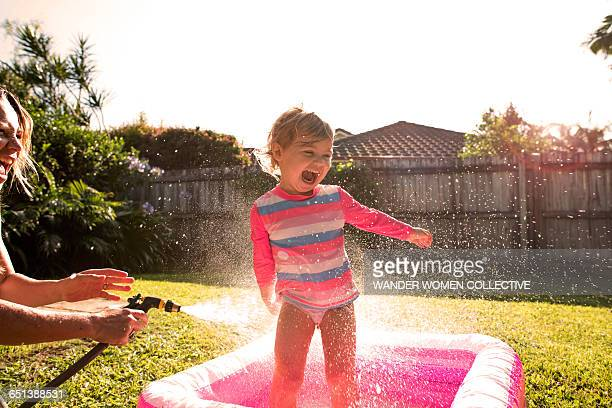 Young girl splashing hose and pool and sunflare