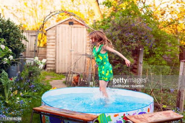 young girl splashing in a paddling pool - playing stock pictures, royalty-free photos & images