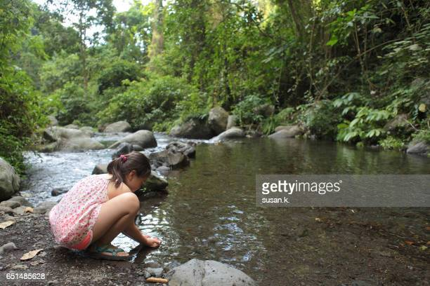Young girl squats and plays with water by the riverbank