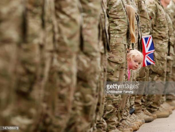 A young girl squeezes between an honour guard of soldiers to get a glimpse of Johnson Beharry VC carrying the Olympic torch at the National War...