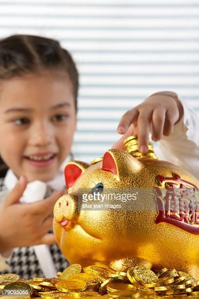 A young girl stacks her golden coins atop a lucky golden piggy bank.