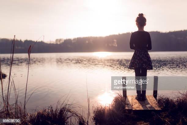 junge Mädchen stehen auf einem Holzsteg am See in Österreich