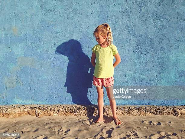 young girl standing alone against a blue wall - blue shorts stock pictures, royalty-free photos & images