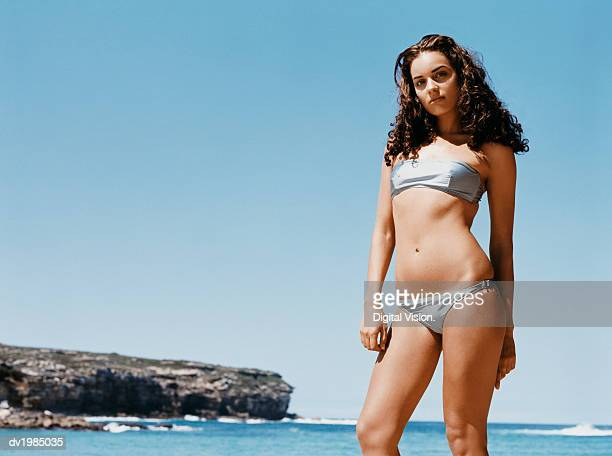 Young Girl Standing at Water's Edge Wearing a Silver Bikini