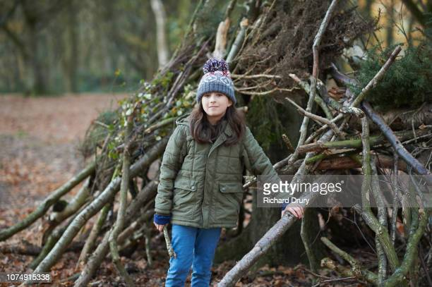 Young girl standing by her den in Autumnal woodland