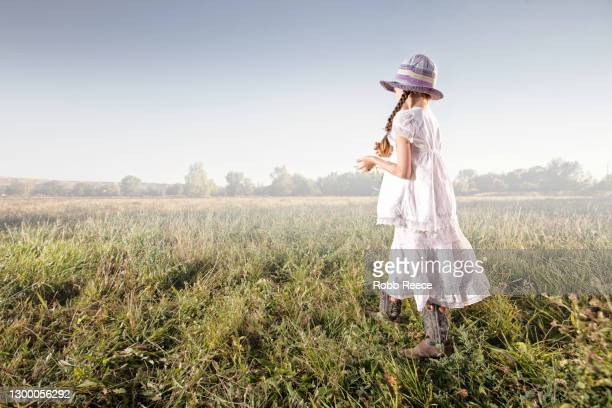 young girl standing in a grass field - robb reece stock pictures, royalty-free photos & images
