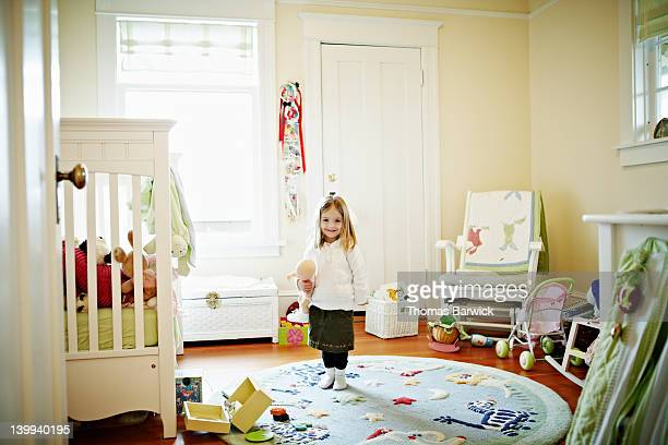 Young girl standing in bedroom smiling