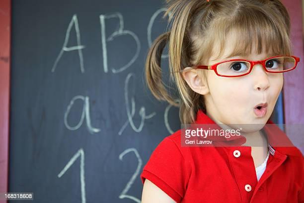 young girl standing in front of a blackboard - wonderkind stockfoto's en -beelden