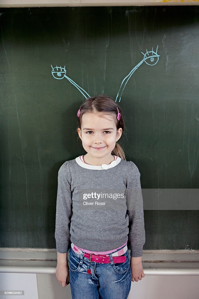 Young girl (6-7) standing in front of blackboard with insect feelers drawn on it : Foto de stock