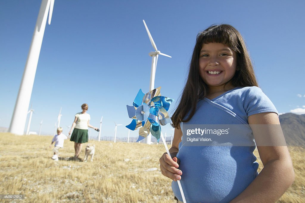 Young Girl Standing in Front of Her Mother and Brother in a Wind Farm : Stock Photo