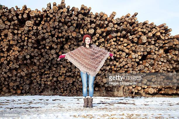 young girl standing in front of stack of logs - girl mound stock pictures, royalty-free photos & images