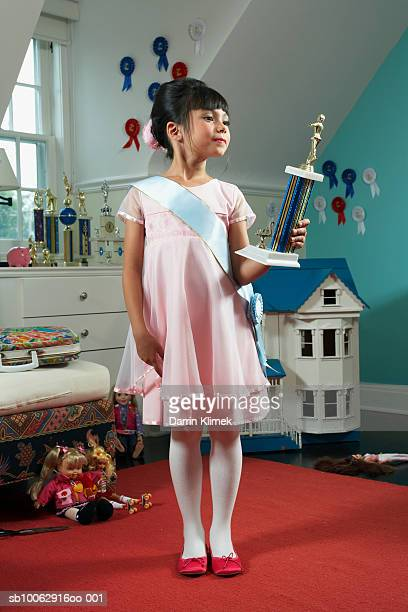 young girl (8-9 years) standing in room wearing dress and sash, holding prize - 8 9 years stock pictures, royalty-free photos & images