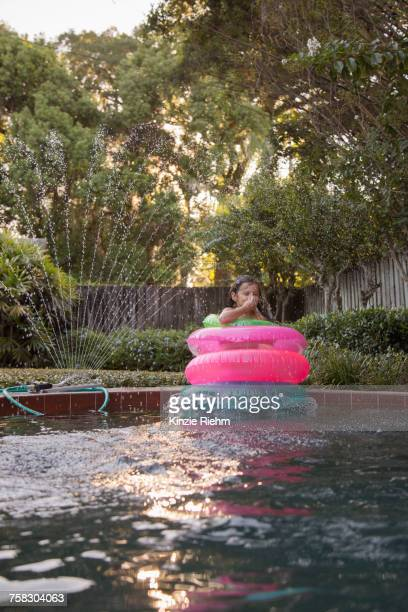 Young girl, standing in the middle of inflatable rings in outdoor swimming pool