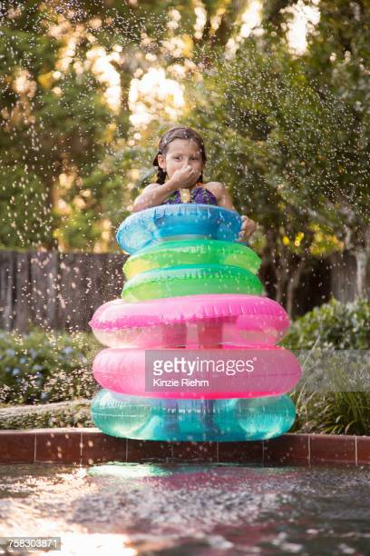 young girl, standing in the middle of inflatable rings on the side of outdoor swimming pool - 鼻をつまむ ストックフォトと画像