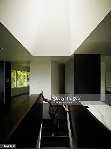 Young girl standing looking up at skylight in home