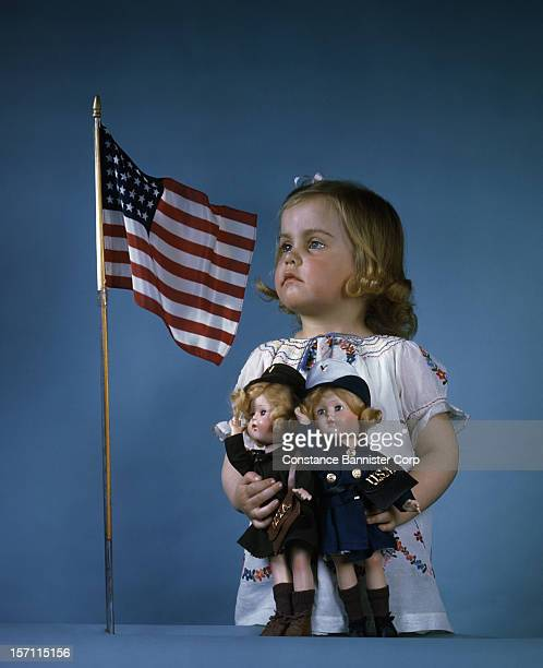 A young girl standing next to a US flag holding two dolls in military uniforms 31st March 1944