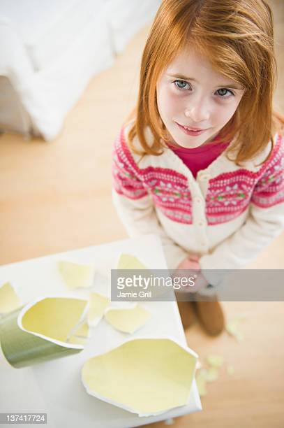 Young girl standing next to broken vase