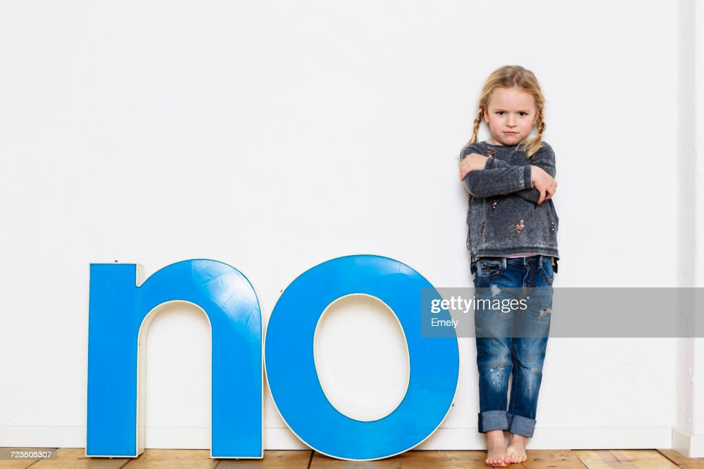 Young girl standing next to large three-dimensional letters, spelling the word NO : Stock Photo