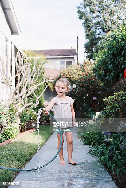 Young girl standing on a path in a garden, playing with a water hose.